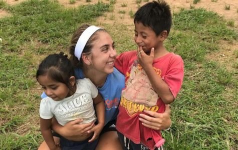 Holding two of the village children, senior Eryn Reesman tickles their tummies. Over the course of the trip, she became close to many of the children, these two in particular.