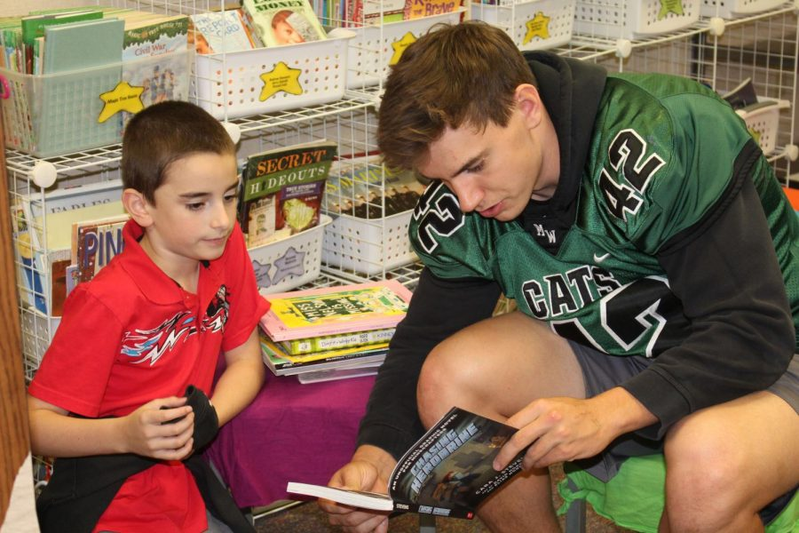 """Senior Alex Johnson spends time individually with a student reading his book.  A defensive standout this season,  he was also able to use his time to volunteer in his community at local schools. """"My favorite part was just helping out the community,"""" Johnson said. """"Seeing ail of their faces light up was great."""" Photo by Haley Renken"""