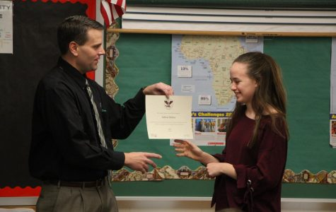 Principal Dr. Greg Tiemann presents Sabrina Delaney with the President's Volunteer Service Award.