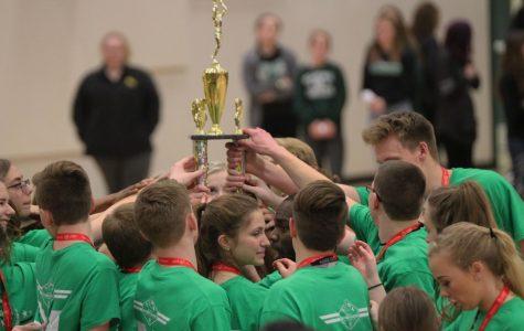 Teammates gather around their shiny new trophy.