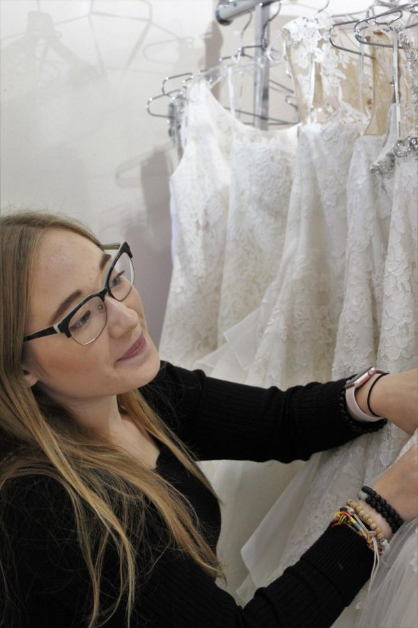 In+the+little+botique+of+Spotlight+Formal+Wear+lies+an+array+of+dresses.+Here+senior+Elizabeth+Sook+searches+the+racks%2C+hoping+to+find+the+perfect+dress+for+her+bride%2C+druing+the+consultation.