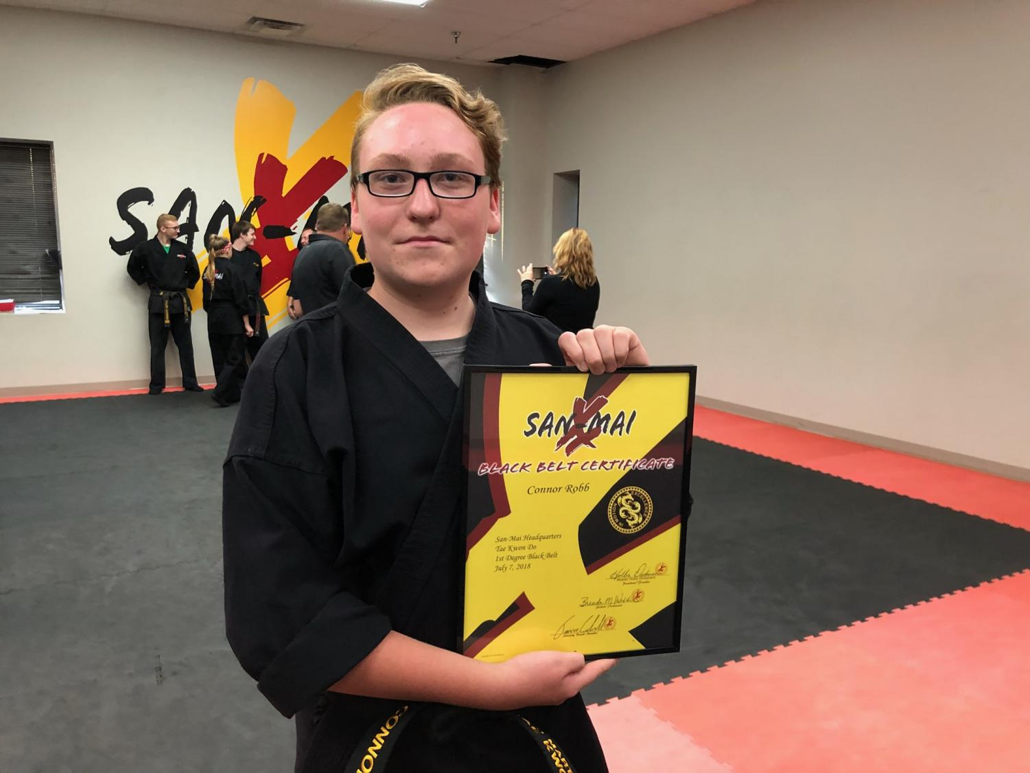 Sophomore Connor Robb holding up his certificate moments after passing the black belt exam.