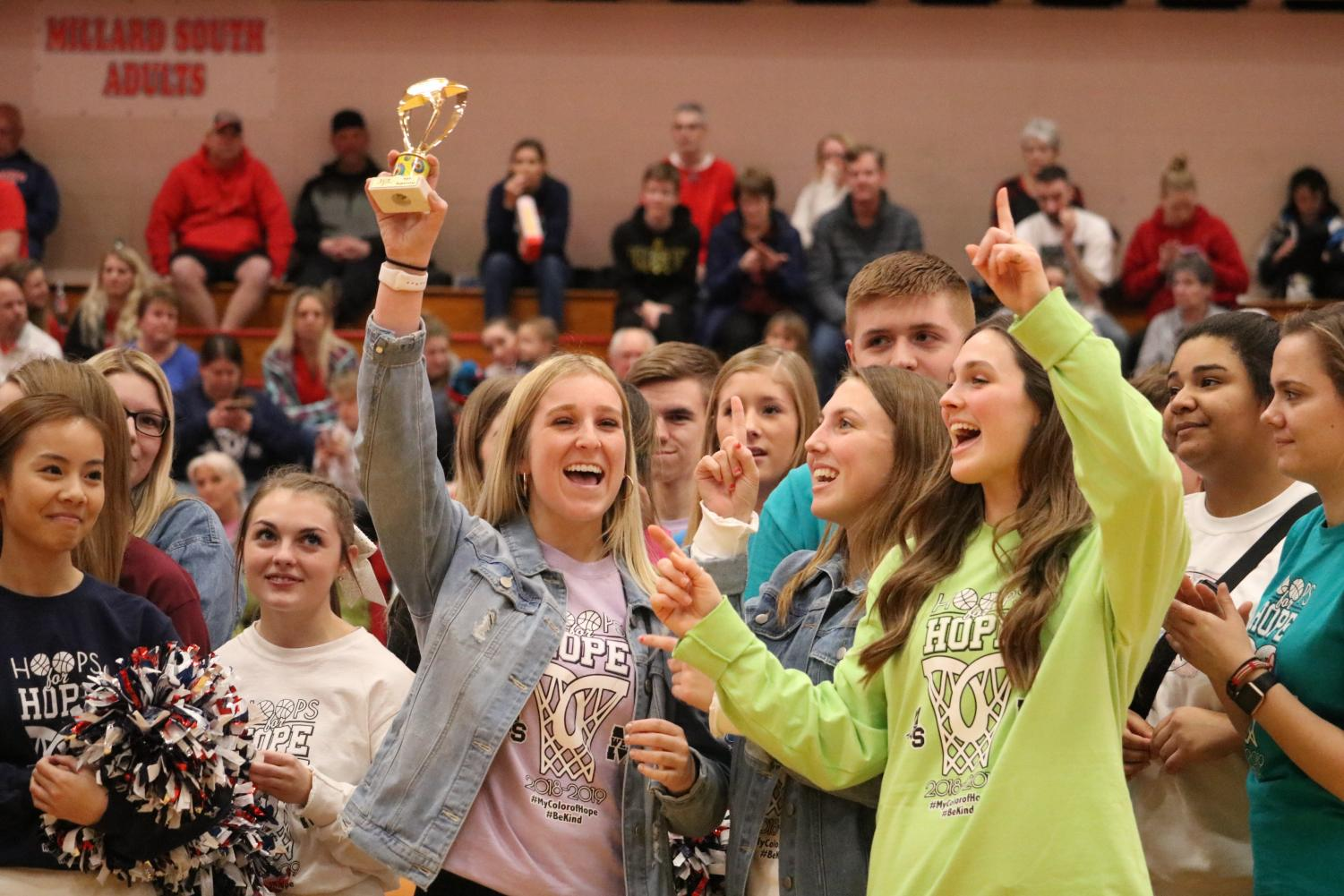 """Smiling wide, senior Chanley Forst accepts the traveling trophy. Forst is a member of Senior Class Board and volunteered to receive the trophy on behalf of Millard West for beating Millard South in a T-shirt selling contest to raise money for the American Cancer Society. """"Accepting the trophy was nerve racking because it was in front of the whole crowd at the basketball game,"""" Forst said. """"I forgot about being nervous when I was actually up there because the money we raised is for such a great cause."""""""