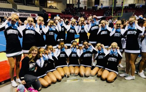 The Millard West Varsity Cheer team poses together holding up both of their metals over their eyes after winning two State titles.