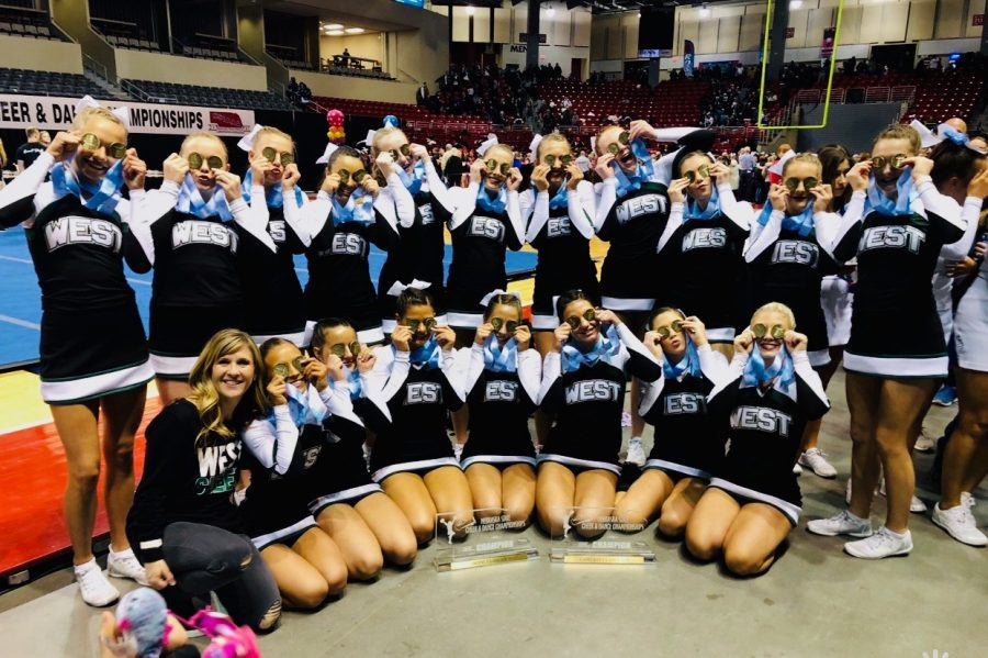 The+Millard+West+Varsity+Cheer+team+poses+together+holding+up+both+of+their+metals+over+their+eyes+after+winning+two+State+titles.