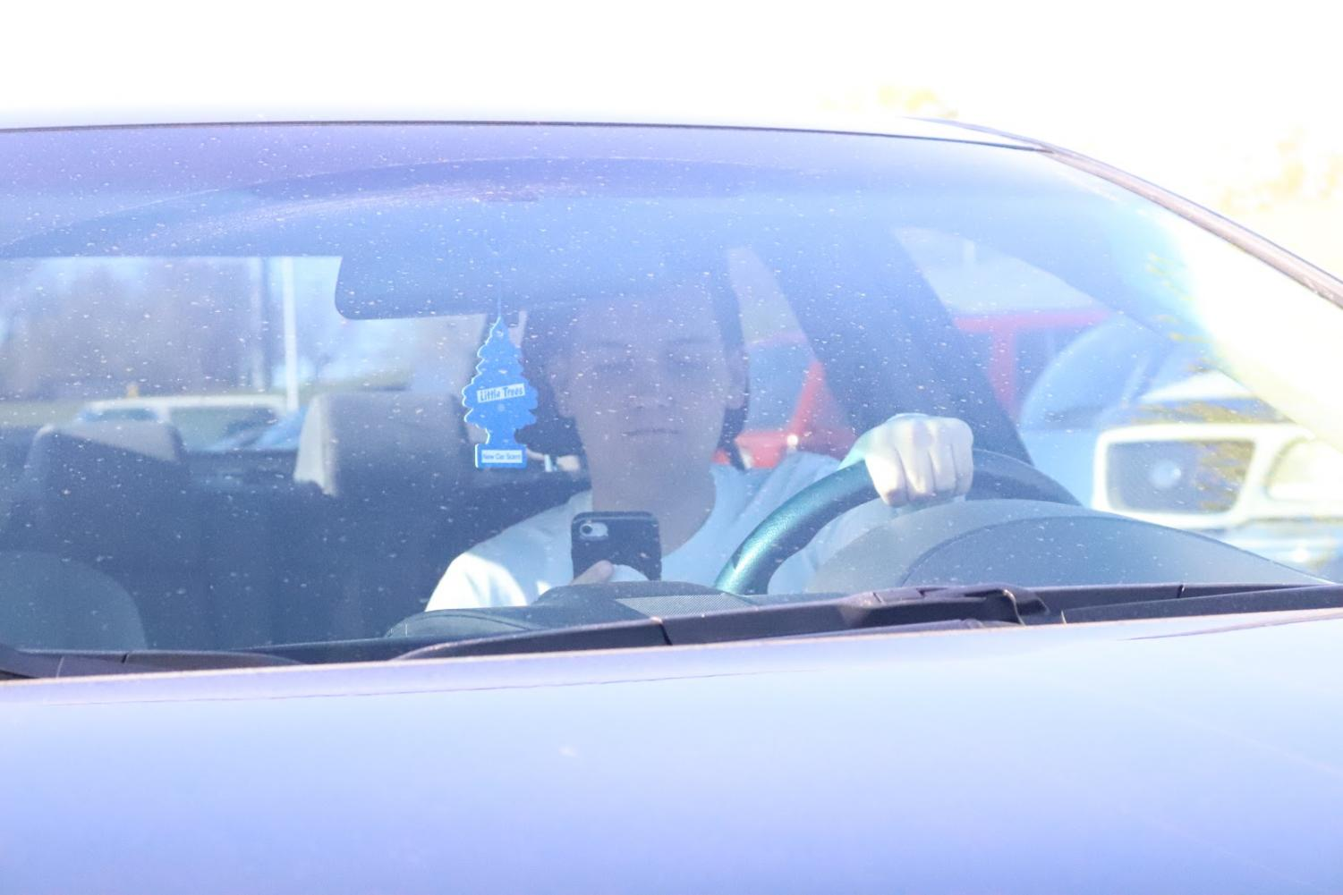 Teenage driver getting distracted by his phone and texting his friends.