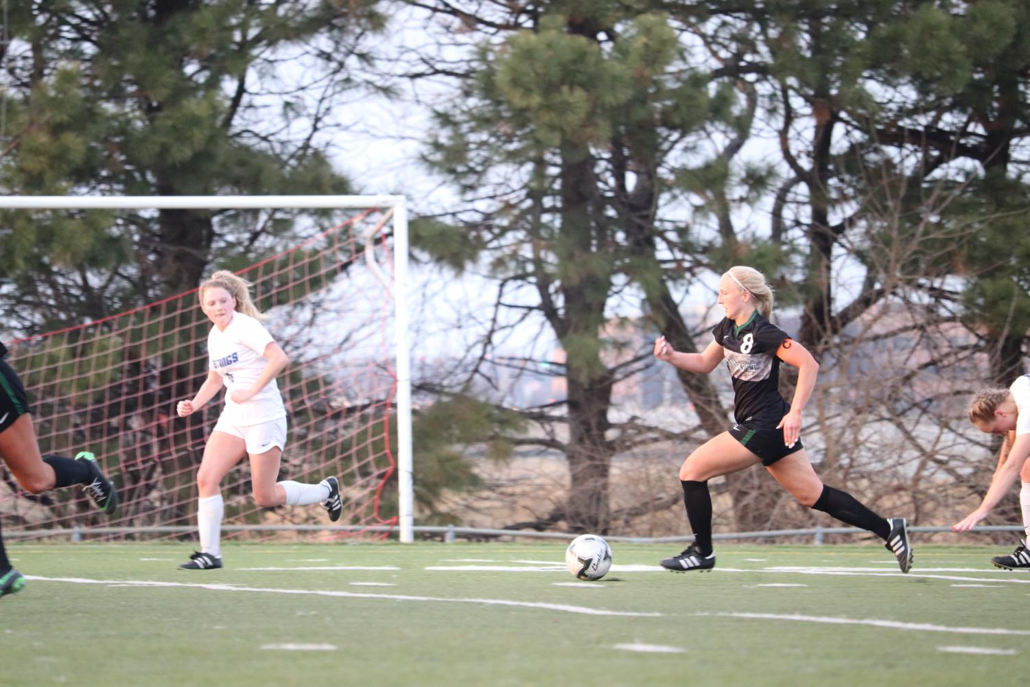 Junior Reagan Raabe dribbles down the field in the second half against Millard North. She scored in their 6-2 win.