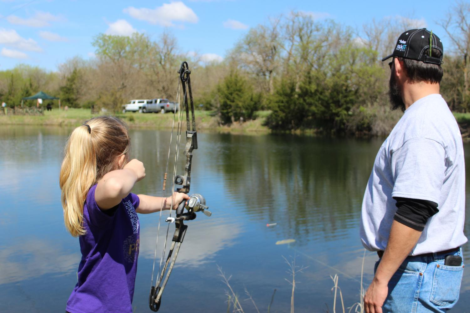 Kearney Outdoor Exploration Expo volunteer instructs student how to use bowfishing equipment.