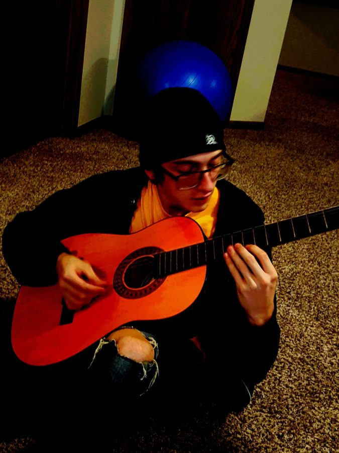 "Junior Gabriel Bennett playing his acoustic guitar. Practicing with his band and writing parts for on of their songs.""I really love to just sit down and just play,'' said Bennett. "" its a great way to learn and try new things on guitar""."