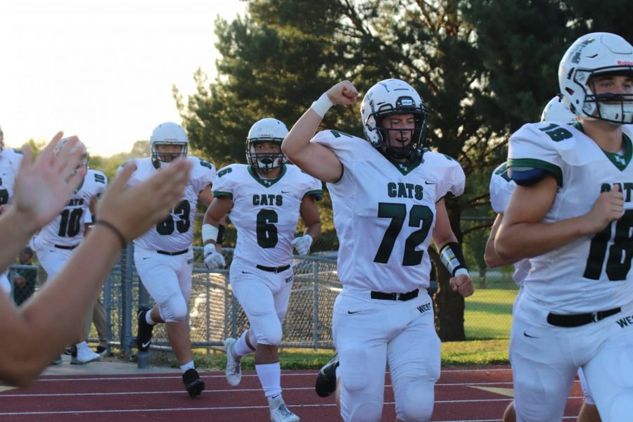 Junior Charlie Aniello cheering while running out onto the field.