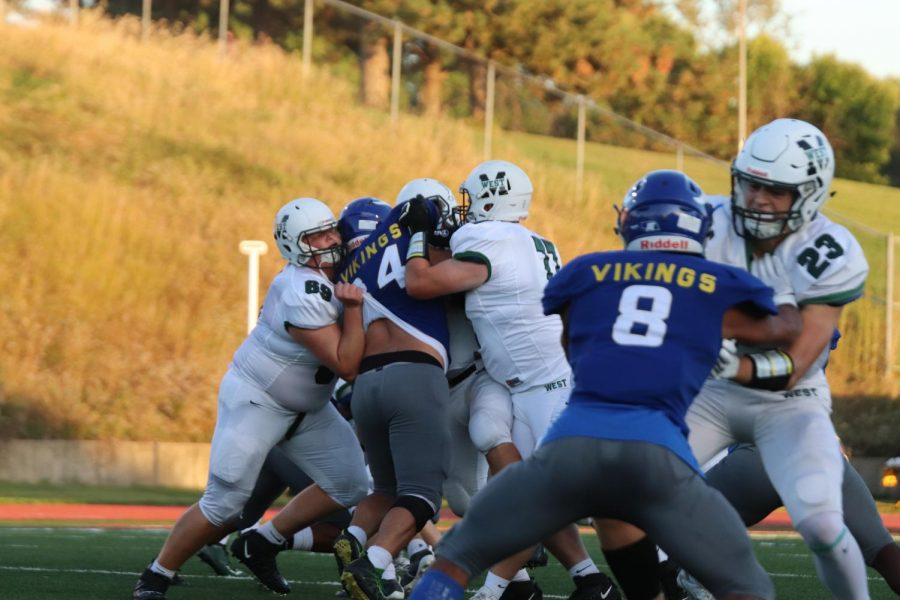 Senior offensive linemen's Noah Klein and Nate Raymond tackling a player.