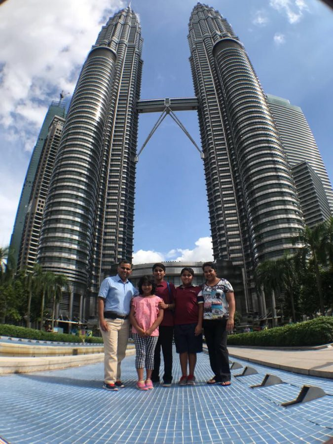 """Aditya Naganna's dad Naganna, sister Artzi, brother Abhay and mother Sushama, stand in front of the Petronas Towers. The 1,483 foot towers have 33,000 stainless steel walls and 52, 000 glass panels. """"When I was standing directly below them, I couldn't see their spires,"""" Naganna said. """"To go up in them, you have to make a special appointment."""""""
