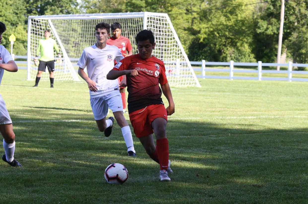 Feeling focused, junior Nasser Nabulsi gets to the ball to kick to his teammate in a game of soccer. He played for the Nebraska futbol club against the team Scott Gallagher from Kentucky.