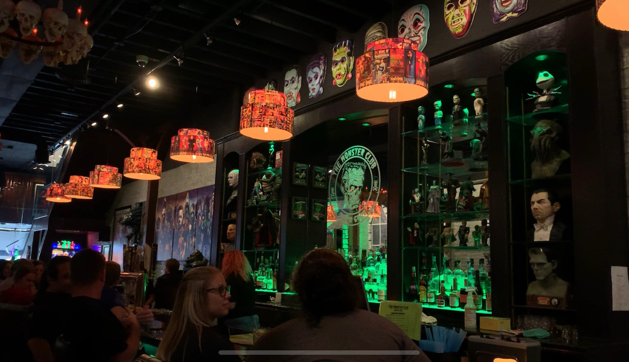 The Monster Club is filled to the brim with some intriguing decor. Here at the center is the main bar area  that contains a large, glowing sign of their brand. The center area is also surrounded by heads of many famous horror movie characters.