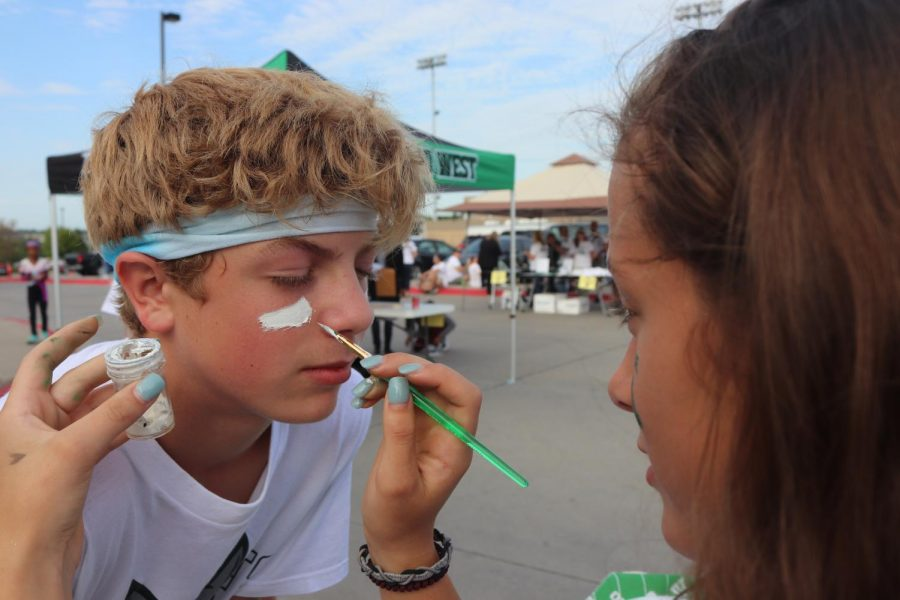 JV cheerleaders applying face paint