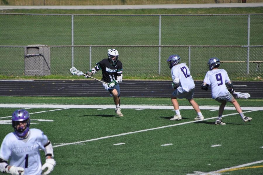 "Doing a clear in a lacrosse game, junior Alexander Rodenbiker (in black) plays lacrosse against the Waukee Warriors. This game was a long and adventurous one, lasting almost three hours. ""Playing in the intense summer heat made this game hard,"" Rodenbiker said. ""I play on the offensive side of my team, which means I have to do a lot of running around the field."""