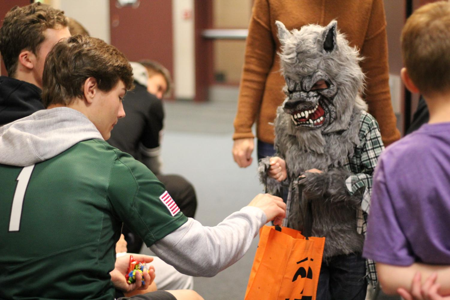 Baseball player, Preston Menicucci helps pass out candy to students.