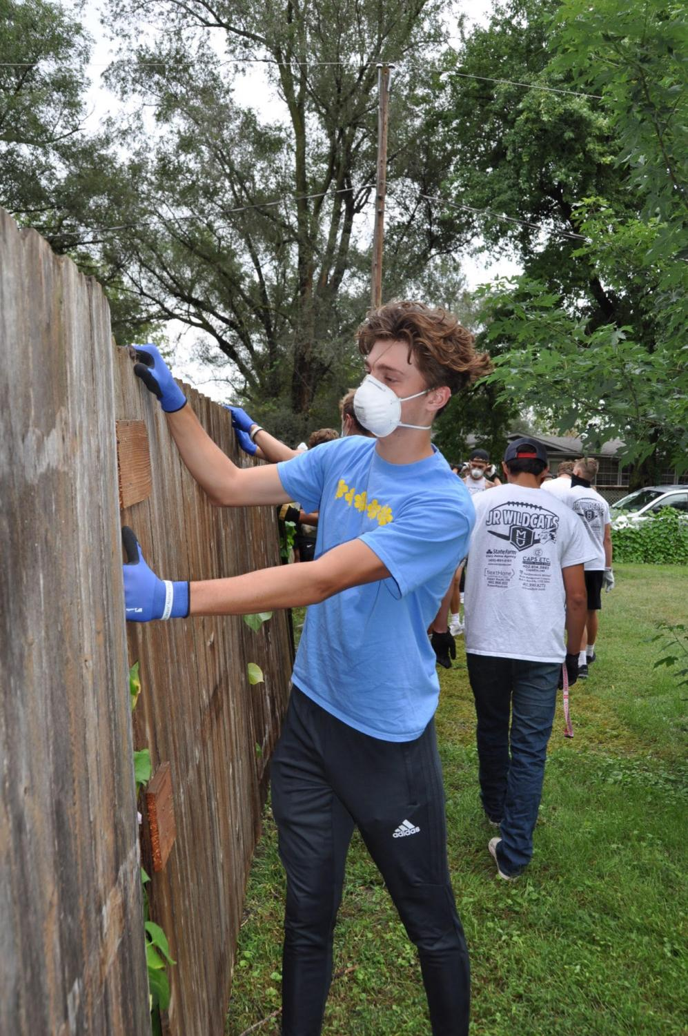 """Junior Dustin Hatch repairs a broken fence with the help of his teammates. He was a part of  the many Millard West varsity football players who helped with flood relief in Valley, Neb. """"The overall experience was very eye opening,"""" Hatch said. """"It made me aware of the amount of damage that had been caused by the flooding. I am glad that I was able to serve a family in need."""""""