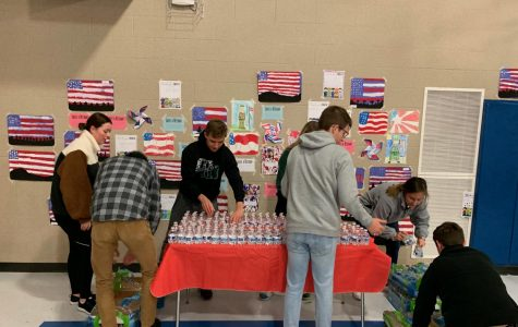 Students are setting up water for the Veteran's Day Performance. They volunteered their time to give back.