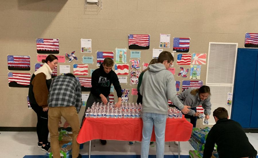 Students+are+setting+up+water+for+the+Veteran%27s+Day+Performance.+They+volunteered+their+time+to+give+back.