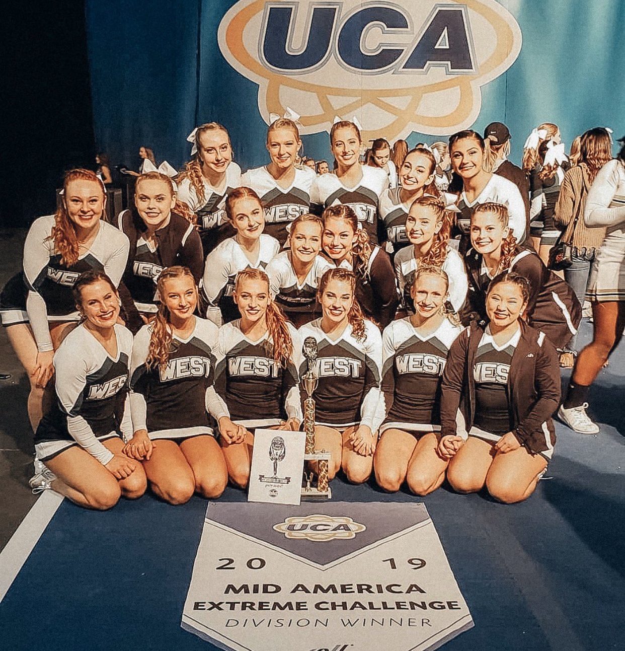 The Millard West Varsity Cheer team poses with their division winner banner along with their first place trophy.