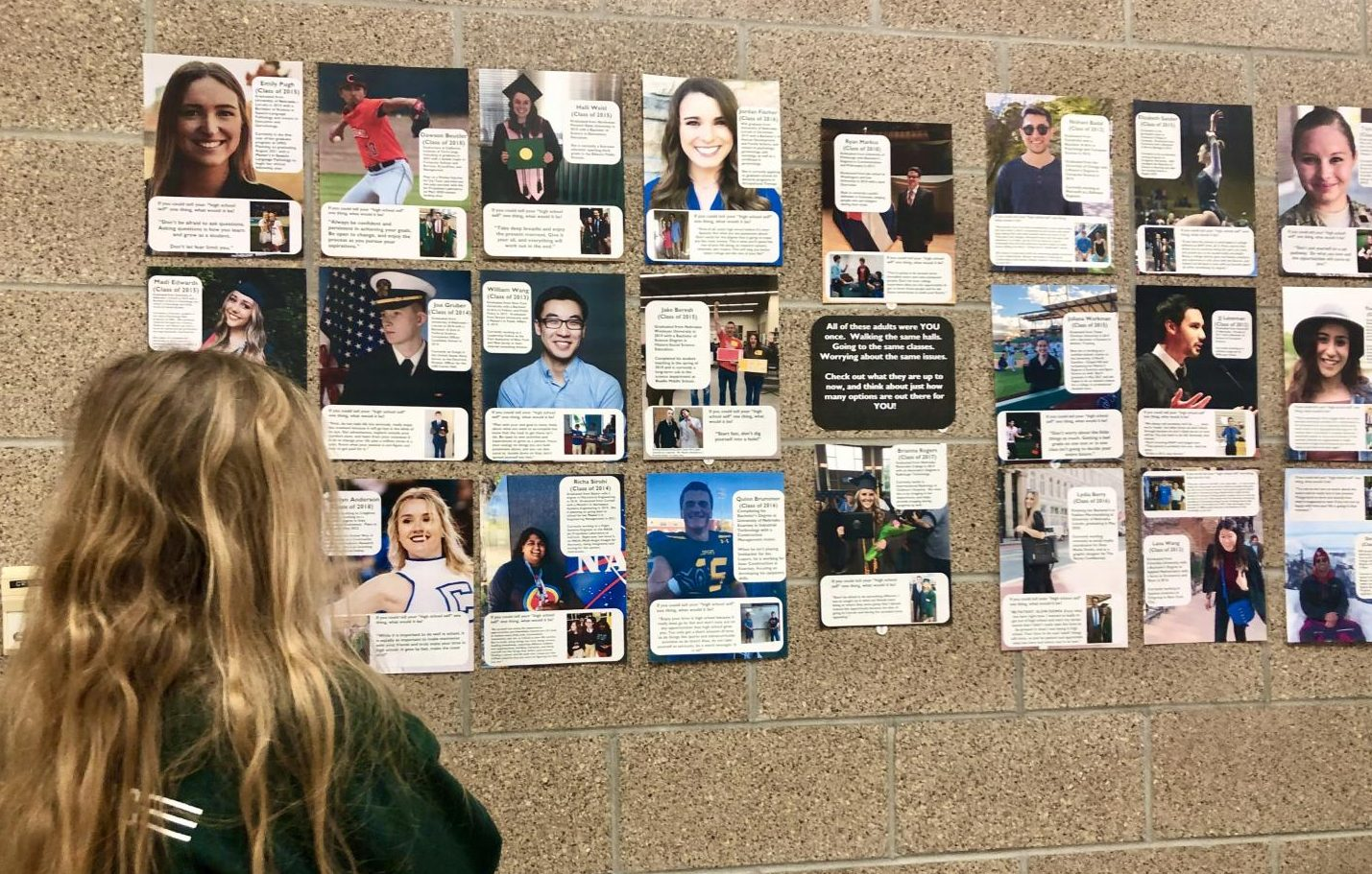 """The alumni display hangs next to room 203. Social Studies teacher Tim Royers intends to cover the entire wall by the end of the year. """"I'll keep expanding as much as I can,"""" Royers said. """"I figure the more examples the better."""""""