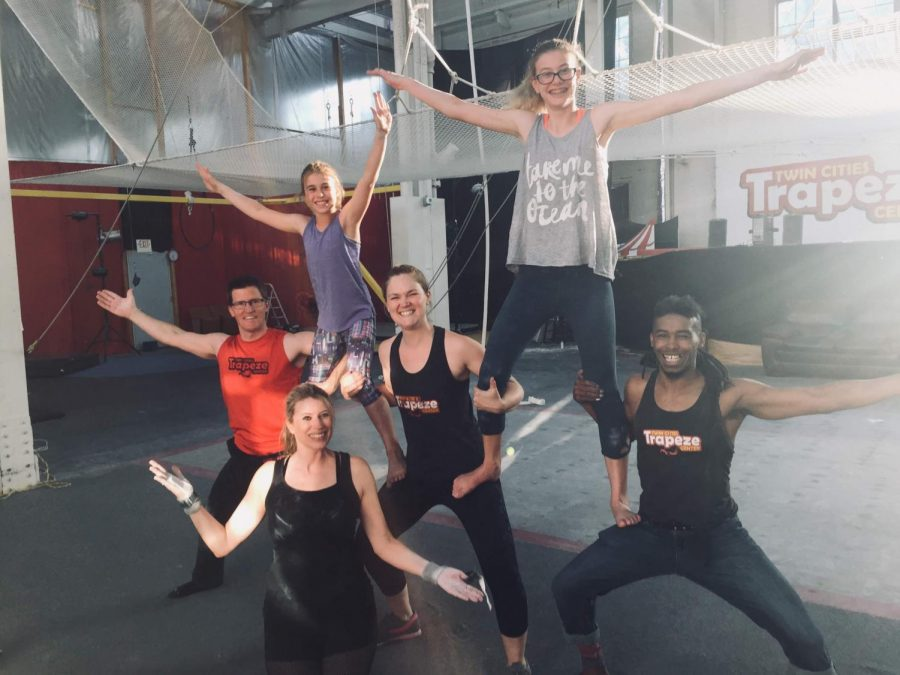 "Sophomore Adison Mullenburg (top right) poses with other trapeze fliers with a bright smile. Being involved in physical activities such as fencing and trapeze has created an outlet for Mullenburg. ""They're both an escape for me, I don't think about anything while flying,"" Mullenburg said. ""I think of nothing during fencing other than what my next move isx and how my opponent is moving."""