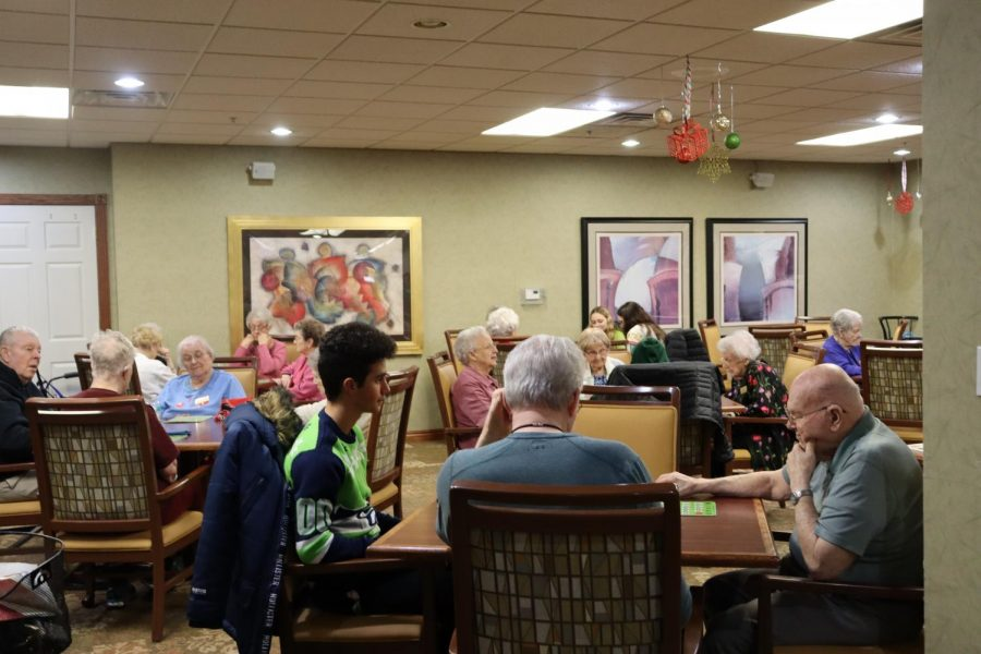 Junior Rami Hanash plays bingo with residents at Walnut Grove Retirement Community. Millard West Student Council visits there frequently and this year they also held a Halloween Bingo.