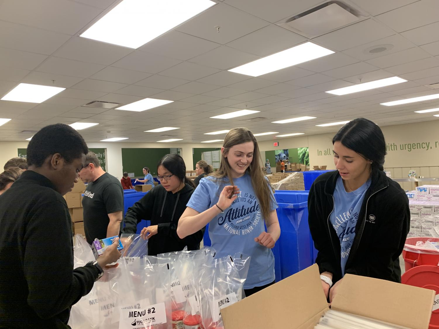 "Members of National Honors Society pack bags with fruit and juice at Food Bank for the Heartland to be donated to families. ""Whenever I have time I always try to do things like this because I really enjoy helping people,"" junior Jordan Bakar said. ""It was fun engaging with people and working with others to help out the community."""
