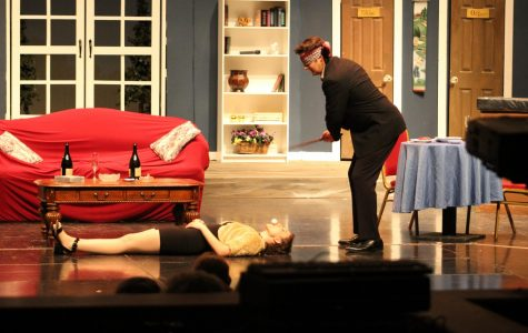 "Senior Hunter Amos (right) lines up a shot as his character Henry Bingham prepares to hit a golf ball blindfolded off of another character's mouth. ""This character was challenging to play because I had to be on stage for much of the show, which meant I had to completely know my lines and keep character nearly every second,"