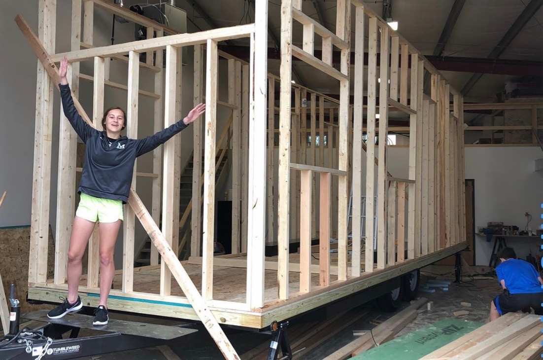 "While working on the frame of the house, junior Elise Nyffeler poses for a photo. The Nyffelers finished building their tiny house in November of 2019, a project they started in the Spring of 2018. ""My family and I have enjoyed hanging out together in our tiny house, and sitting down with friends and playing games inside,"" Nyffeler said. ""I am excited for future memories we will make in it."""
