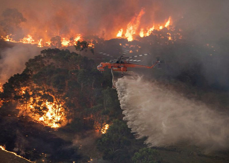 Battling the fires, the firefighters use any means necessary to control and contain the fires. A helicopter tackles a fire in East Gippsland, Victoria state, Australia.