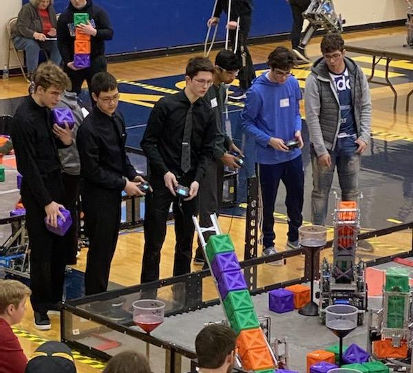 """Controlling and stacking up blocks with their robot, juniors Mike Nigrila, Mark Schaffer and senior Luke Hartman participate at VEX State Robotics Championship at Omaha North High School. Their competition was an overall success for Millard Wests robotic teams. """"Friday night was stressful, not knowing how the skills competition would pan out for us,"""" junior Mark Schaffer said, """"We had no idea how many points we would make out with, and were a bit anxious."""""""