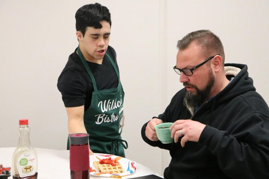 """Being given his meal of waffles by Senior Ferdinando Andrade, teacher William Fredrickson enjoys his time at the Bistro. The Wildcat Bistro is an event made for the ACP students to get real-life experiences. """"The Bistro was very enjoyable with great food and good company,"""" said Watson. """"It was organized very nicely."""""""