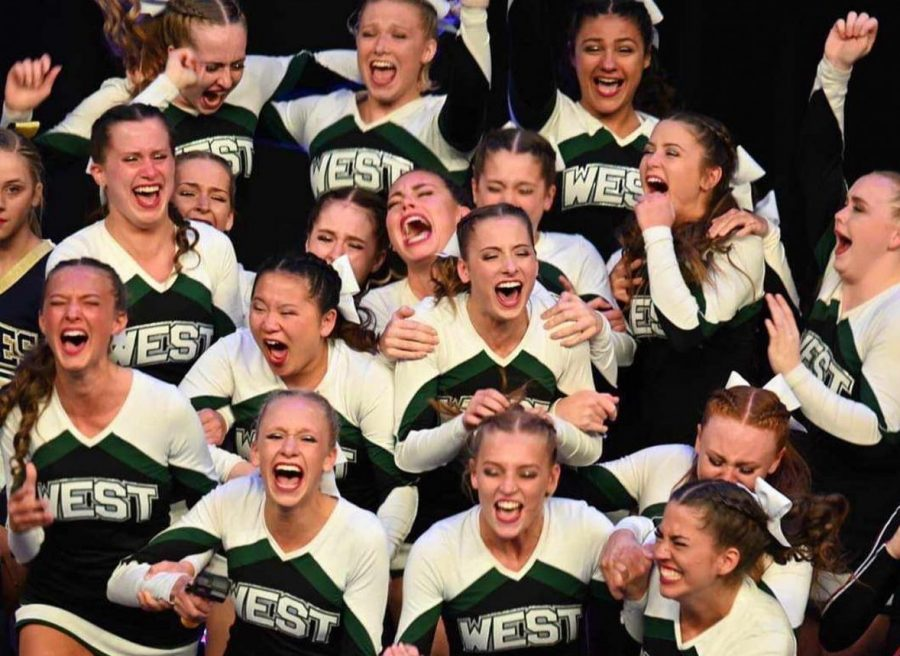 In+this+picture+the+Millard+West+Varsity+Cheer+team+just+found+out+that+they+had+won+at+state.+They+won+with+both+their+Tumbling+and+Game+Day+routine.+%22My+favorite+thing+about+cheer+is+the+bonds+I+build+and+performing%2C%22+Sophomore+Brenna+Matthews+said.+%22I+love+being+out+on+stage+and+learning+what+else+I+can+do+to+fix+my+mistakes+and+get+better.%22