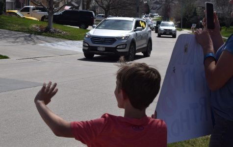 "Second-grader Everett Nyffeler helps hold up a sign and waves to the line of cars passing by. The staff of Wheeler Elementary hosted this drive-by parade to let kids know that teachers are still thinking about them. ""I made a 'Honk for my 8th birthday' sign,"" Nyffeler said. I also had a poster that my brother and sister held that said 'Hello Wheeler Teachers.'"""