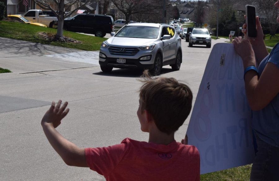"""Second-grader Everett Nyffeler helps hold up a sign and waves to the line of cars passing by. The staff of Wheeler Elementary hosted this drive-by parade to let kids know that teachers are still thinking about them. """"I made a 'Honk for my 8th birthday' sign,"""" Nyffeler said. I also had a poster that my brother and sister held that said 'Hello Wheeler Teachers.'"""""""
