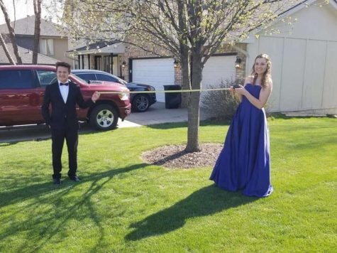 Tomm Bigler and his date, Mae Killeen keep social distancing while taking pictures to recreate their prom night.