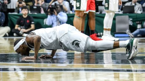 Michigan State senior guard Cassius Winston kisses the floor after checking out on senior day, a Spartan tradition, during their game against the Ohio State Buckeyes. Little did Winston know this would be his last time on the floor wearing a Spartans uniform.