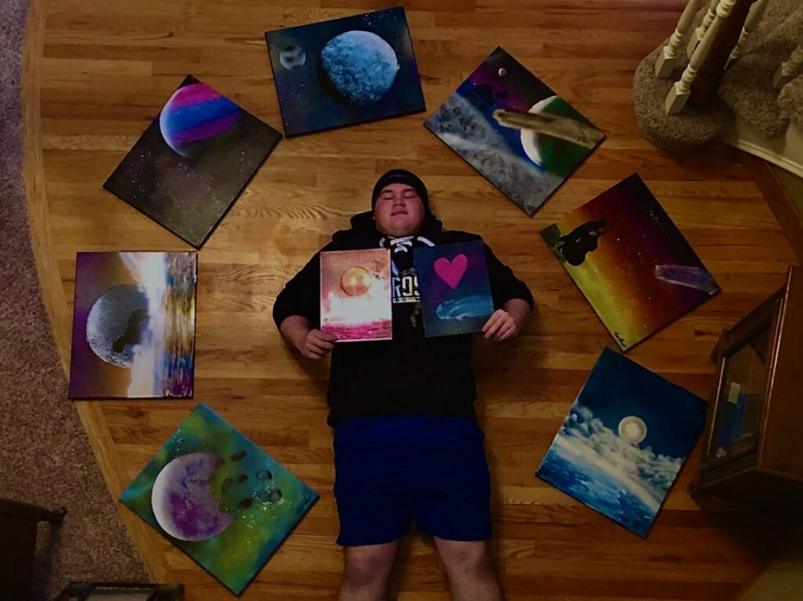 "Photo of Senior Owen Berreth surrounded by the art posted on his Instagram @lil_intro_vert__. ""I'm really proud of how I've improved and am able to share my art,"" Berreth said. ""it's just good to see a positive reaction to my art and lets me see that my art is worth the time I spend on it."""