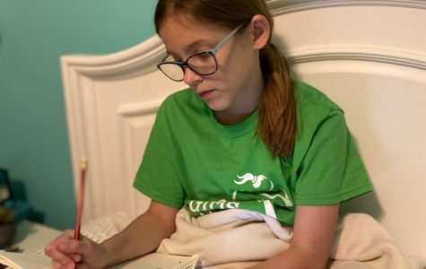 Fifth grader Anna Jetter sits in her bed and does her online learning. She has missed her friends and teachers during her time away from school.