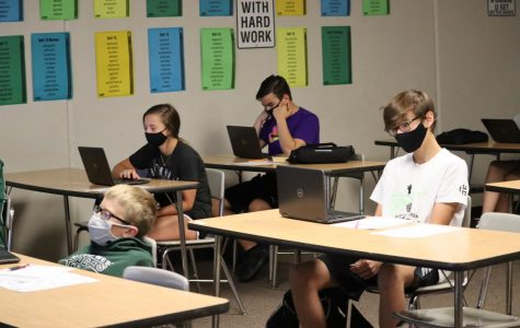 Students in room 131 learn on their computers while they are in person. Every student is wearing a mask.