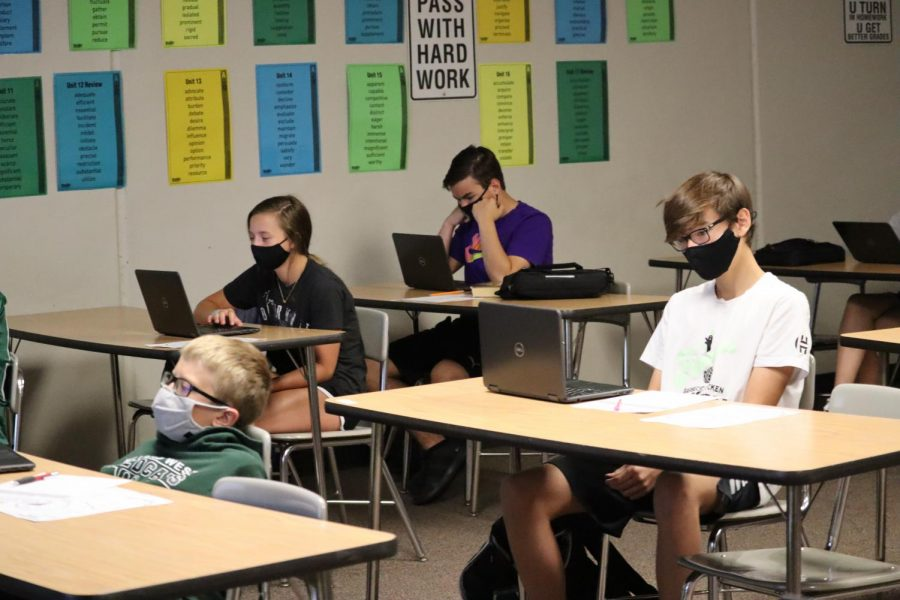 Students+in+room+131+learn+on+their+computers+while+they+are+in+person.+Every+student+is+wearing+a+mask.+