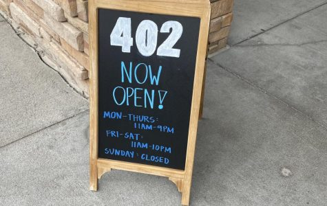 402 Eat + Drink opened August 11th . This sign sits outside on their front door step giving the hours and operations for the restaurants and welcoming the customers in.