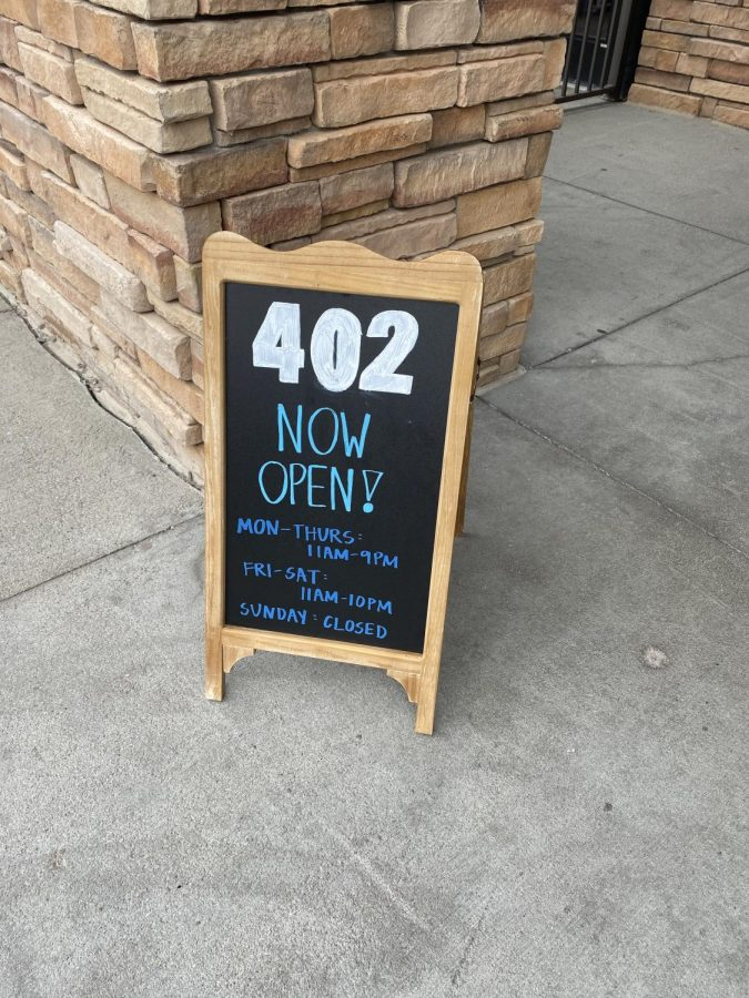 402+Eat+%2B+Drink+opened+August+11th+.+This+sign+sits+outside+on+their+front+door+step+giving+the+hours+and+operations+for+the+restaurants+and+welcoming+the+customers+in.+