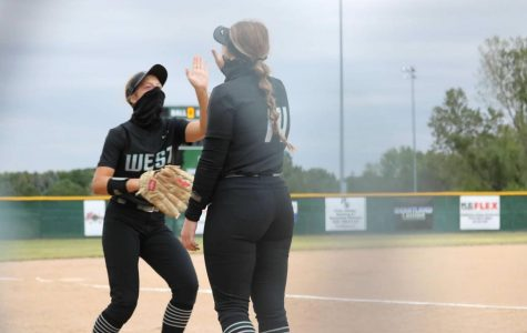 Junior Ava Rongisch and senior Madi Warren look up at each other while wearing a mask. They stood on the softball field getting ready to play.