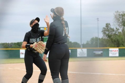 "Junior Ava Rongisch and senior Madi Warren look up at each other while wearing a mask. They stood on the softball field getting ready to play. ""When it is hot out, the gator mask does get pretty sweaty,"" junior Ava Rongisch said. ""Also, when we are done running and have to put up our mask it makes it a little hard to breathe. We all know it's for our safety."""