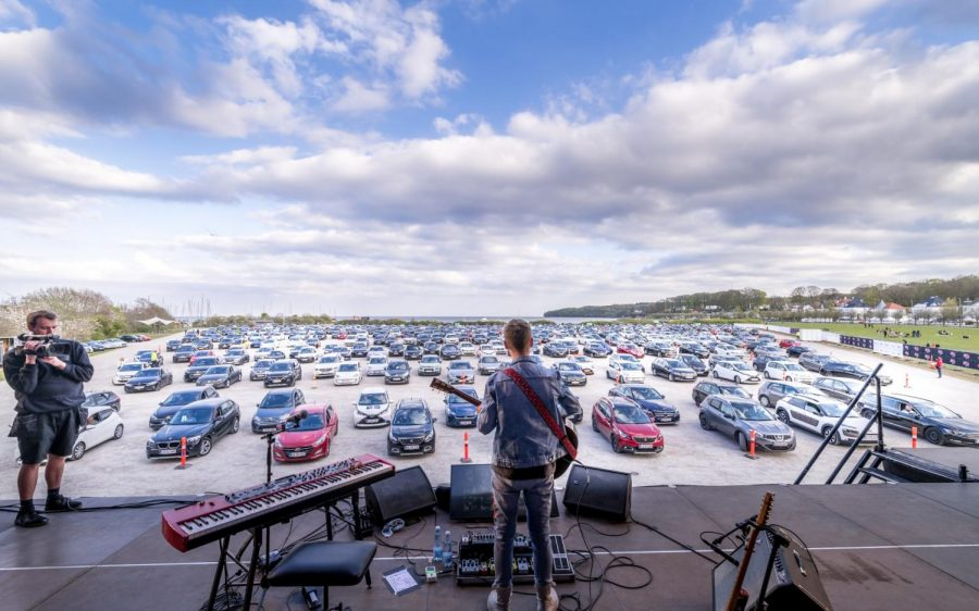 Cars lined up and distanced from each other at the new outdoor venue in Denmark show another way people can safely enjoy live music. People at the concert are able to connect to a private FM radio station so that they can hear the performer in their car.