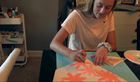 """With a paintbrush in hand and her craft cart at the ready, senior Elise Nyffeler works on one of her custom banners. After a customer places an order, she tries to get the banner done within one week. """"I usually work on four or five banners at a time,"""" Nyffeler said. """"I always cut a batch of mini, regular and large banners before I start. I will paint the background of one, and then work on the next one while that one dries."""""""