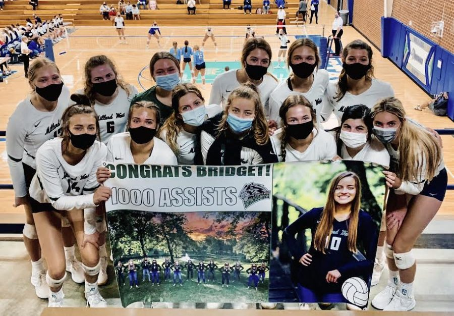 The+varsity+volleyball+team+holds+up+a+banner+for+senior+Bridget+Smith.+During+the+first+game+of+the+Millard+North+invite%2C+Smith+reached+the+milestone+of+1%2C000+assists+throughout+her+time+as+a+Wildcat.+%E2%80%9CAll+achievements+should+be+recognized%2C%E2%80%9D+head+coach+Joe+Wessel+said.+%E2%80%9CWe+love+giving+our+athletes+their+time+to+shine.+We+post+many+blurbs%2C+photos+and+videos+on+our+Twitter+and+Facebook+pages+because+our+student-athletes+put+in+the+work+and+we+want+them+to+be+recognized.%E2%80%9D